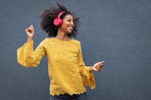 happy woman dances in headphones after anxiety treatment in greenwood, IN at renewed hope counseling services