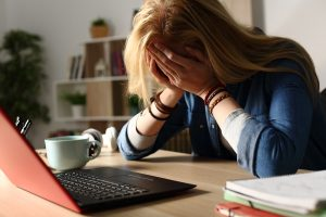 sad woman with her head in her hands at her desk. She goes to trauma treatment and PTSD treatment in Greenwood, IN at Renewed Hope Counseling services for ptsd symptoms 46143