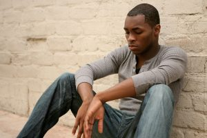 sad african american man leaning against a wall before getting ptsd treatment and trauma treatment in Greenwood, IN for ptsd symptoms at Renewed Hope Counseling services 46143