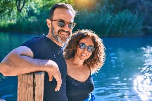 happy couple by a lake smiles at the camera while wearing sunglasses. They got couples counseling and marriage counseling in Greenwood, IN at Renewed Hope Counseling Services 46143