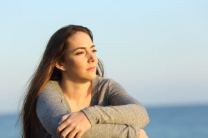 serious woman sits by a lake before anxiety treatment in greenwood, in at renewed hope counseling center 46143