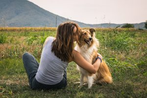 woman sits in a field and kisses her dog. She found relief in trauma treatment in greenwood, IN for PTSD symptoms at Renewed hope counseling services 46143