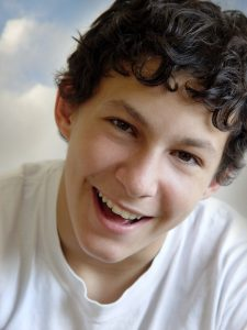 happy teen boy after teen counseling in greenwood and working with a teen therapist in at renewed hope counseling 46143