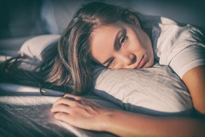 White woman with long brown hair lays on her pillow and looks towards the camera. She looks very depressed, her eyes filled with grief from losing a loved one. Renewed Hope Counseling Services offers grief counseling in Greenwood, IN