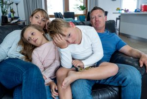 unhappy family sitting on the couch after arguing frequently. They got family therapy in Greenwood, IN at Renewed Hope Therapy 46143